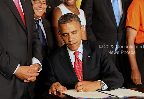 United States President Barack Obama signs HR 4348, which includes transportation and student loan interest rates bills in the East Room of the White House in Washington, D.C. on July 6, 2012.  The bill will put Americans to work repairing the nation's crumbling roads and bridges and will prevent student loan interest rates from doubling for more than 7 million students. .Credit: Molly Riley / Pool via CNP