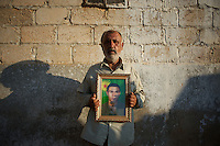 August 12, 2012 - Kafa Safra, Efrin, Syria: Barakat Gadalum, father of a dead Kurdistan Workers' Party (PKK) fighter, poses with his son's portrait. Around five thousand Syrian Kurdish attended the funeral and ceremony of martyrdom of Taliz Gadalum, killed days earlier during combat against the Turkish army...PKK has been fighting an armed struggle against the Turkish state for an autonomous Kurdistan and greater cultural and political rights for the Kurds in Turkey, Iraq, Syria and Iran. Founded on 27 November 1978 in the village of Fis, was led by Abdullah Öcalan. The PKK's ideology was originally a fusion of revolutionary socialism and Kurdish nationalism - although since his imprisonment, Öcalan has abandoned orthodox Marxism. The PKK is listed as a terrorist organization by Turkey, the United States, the European Union and NATO. (Paulo Nunes dos Santos/Polaris)