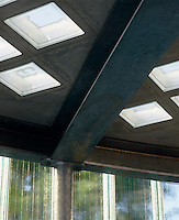 A dining room where the stainless steel ceiling is punctuated with skylights in the form of glass bricks and one wall is constructed entirely from frosted glass
