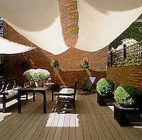 Three sail-cloth awnings provide shade in this decked courtyard garden
