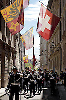 Switzerland. Geneva. Old town. A group of recruits (policemen and policewomen) from the police academy march on the day in which they will be all sworn in as police officers. They wear uniforms, white gloves, tricorns on the heads and carry old rifles with bayonet on the shoulders. The tricorne or tricorn is a style of hat that was popular during the 18th century, falling out of style by 1800. The tricorne was worn as part of military uniforms. A bayonet (from French ba&Ccedil;onnette) is a knife, sword, or spike-shaped weapon designed to fit in, on, over or underneath the muzzle of a rifle, effectively turning the gun into a spear. The flag of Switzerland consists of a red flag with a white cross (a bold, equilateral cross) in the centre. It is a sovereign-state flag. The flag of Geneva is divided vertically into two equal parts, yellow (hoist) and red (fly). In the hoist, a black double-eagle with a red crown, beak, tongue, legs and claws, cut in half by the palar line. In the fly, a yellow upright key with its ward toward the fly. The eagle symbolises loftiness, justice and protection. The key symbolises ecclesiastical rule, treasuries, and responsibility. The arms of Geneva are actually two shields impaled: half the eagle of the Holy Roman Empire, and one of the two keys of St. Peter (the &quot;keys of heaven&quot;). 29.08.12 &copy; 2012 Didier Ruef...