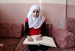 Asmaa Abu Hilal,18, a Palestinian blind student reads a copy of the holy Koran in braille at her family house in Rafah in the southern Gaza strip on Feb. 14, 2017. Abu Hilal superior at her study although there are no private schools for the blind in the city of Rafah. Photo by Ebtehal Shurab