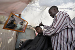 A barber has set up his new barber shop in a camp for homeless families set up on a golf course in Port-au-Prince, Haiti, which was ravaged by a January 12 earthquake.