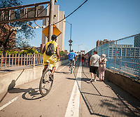 Unicyclists share space with pedestrians during their ride across the Brooklyn Bridge for their 13-mile trip to Coney Island on Friday, August 29, 2014 as part of the NYC Unicycle Festival. The convergence of unicyclists was the start of the 3-day Fifth Annual New York City Unicycle Festival which besides the ride, features performances, classes and just plain fun with events happening on Governor's Island. (© Richard B. Levine)
