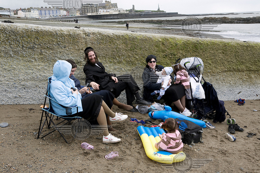 An Hasidic family relax on North Beach, as the clouds gather in Aberystwyth..