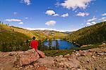 Man overlooking Upper Sardine Lake, Sierra County, Northern California.