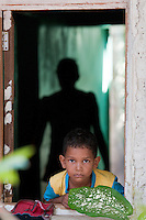 Child in window of his home. Mauritius.