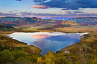 The vivid colors of an autumn sunrise are mirrored in the waters of Catamount Lake near Steamboat Springs, Colorado.
