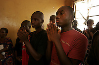 Youths take part in a religious service in the 'City of Rest', a rudimentary counselling and mini rehabilitation centre for recovering drug addicts, alcoholics and traumatised or delinquent youths.  It is run by a pastor who attributes the centre's success to the extensive rest, food and prayer. © Fredrik Naumann Freetown, Sierra Leone.