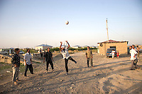 Men hit a soccer ball in a camp for internally displaced people from Nagorno-Karabakh; Agdam region, Azerbaijan.