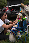 Native American , Chaske Hill Sicangu Lakota and Seneca , smiling mother dressing and preparing  her 3 year old son for pow wow dance contest at the Thunderbird powwow in Queens, NY .