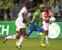 Eddie Johnson, right, of the Seattle Sounders FC battles Andrew Jean-Baptiste for the ball during play at CenturyLink Field in Seattle Saturday August, 3, 2013. The Sounder won the match 1-0.
