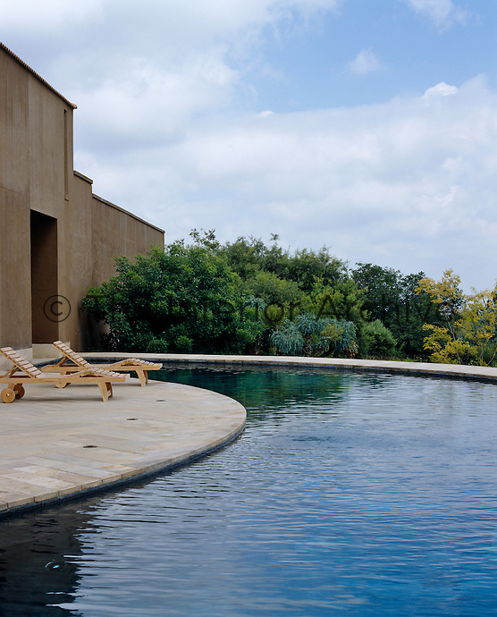 The walls of the house provide a backdrop for the island-like curved terrace which juts out into the semi-circular swimming pool