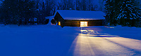 Panorama of yellow light spilling out of a log cabin window on the snow in Wiseman, Alaska,