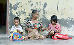Saridia Waruwu helps her grandson Jesta, 4, and her granddaughter Cari, 8, do their homework in front of her home in Tugala, a village on the Indonesian island of Nias. <br /> <br /> The village was struck by both a 2004 tsunami and a 2005 earthquake, leaving houses destroyed and lives disrupted. The ACT Alliance helped villagers here to construct new homes and latrines, build a potable water system, open a clinic and schools and get their lives going once again. For the residents of Tugala, the post-disaster mantra of &quot;build back better&quot; became a reality with help from the ACT Alliance.