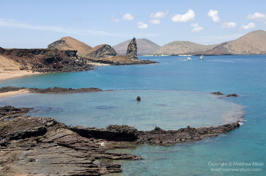 Bartolome Island, Galapagos, Ecuador; view of Pinnacle Rock and a volcanic crater in the lagoon near the entrance to the path leading to the summit of Bartolome Island , Copyright © Matthew Meier, matthewmeierphoto.com All Rights Reserved