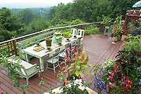 Home deck on two levels, with beautiful table set for eating outside, custom made touches, planters of flowers and containers of vegetables, rose garden, incredible view