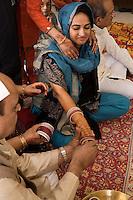 Delhi, India, 21 gennaio 2011. Matrimonio di Sumedha e Sapan. Durante le celebrazioni propiziatorie per la sposa.  A Sumedha viene fatta indossare una fila di bangles per ogni braccio. Essi rappresentano uno dei simboli più importanti dell'unione matrimoniale. Secondo la tradizione i bracciali andrebbero portati per un anno.