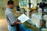 China. Province of Zhejiang. Hangzhou. A potential buyer looks at the construction's draught  for a new real estate project development. A scale model of the complete future housings has been built up in order to give buyers a better idea on how will look their new residence and surroundings. © 2004 Didier Ruef