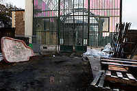New Caledonia Glasshouse (formerly The Mexican Hothouse), 1830s, Charles Rohault de Fleury, Jardin des Plantes, Museum National d'Histoire Naturelle, Paris, France. Low angle view  showing building works in front of the glass and metal structure, in which is reflected the Plant History Glasshouse (formerly Australian Glasshouse), 1830s, Rohault de Fleury, bathed in the late afternoon light. The New Caledonia Glasshouse, or Hothouse, was the first French glass and iron building.