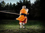 Portrait of a Shaolin warrior monk spinning with a staff practicing a Kung Fu long weapon form