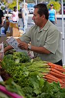 Farmers' market vendor Claudio adjusting a sign. SR.