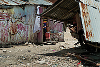 Haitian girl stands in the door of a shack in the slum of Cité Soleil, Port-au-Prince, Haiti, 16 July 2008. Cité Soleil is considered one of the worst slums in the Americas, most of its 300.000 residents live in extreme poverty. Children and single mothers predominate in the population. Social and living conditions in the slum are a human tragedy. There is no running water, no sewers and no electricity. Public services virtually do not exist - there are no stores, no hospitals or schools, no urban infrastructure. In spite of this fact, a rent must be payed even in all shacks made from rusty metal sheets. Infectious diseases are widely spread as garbage disposal does not exist in Cité Soleil. Violence is common, armed gangs operate throughout the slum.