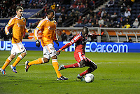 Chicago forward Dominic Oduro (8) gets off a shot in front of Houston defenders Jermaine Taylor (4) and Bobby Boswell (32).  The Houston Dynamo defeated the Chicago Fire 2-1 in the Eastern Conference play-in game for the MLS Playoffs at Toyota Park in Bridgeview, IL on October 31, 2012.