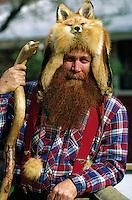 A man portrays an Alaskan 'Sourdough' (early settler prospector  mountain man,) posing in a fox hat, holding a carved walking stick. Alaska.