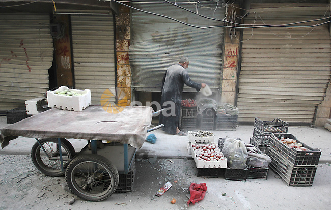 A Syrian man cleans up his store after a missile fired by Syrian government forces hit a residential area in the al-Sukari district in the northern Syrian city of Aleppo on September 15, 2015. Photo by Ameer al-Halbi