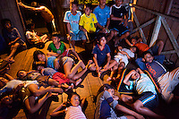 An Indigenous family host children who traveled via canoe at night to watch a movie on TV powered by a generator with gasoline borrowed from the first tourist to visit the community  - Communidad Siete de Augosto - Amazonas - Colombia