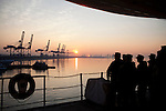 Sailors watch the sunrise on board the USNS Comfort, a naval hospital ship, before it gets under way to Haiti to assist earthquake victims on Saturday, January 16, 2010 in Baltimore, MD.