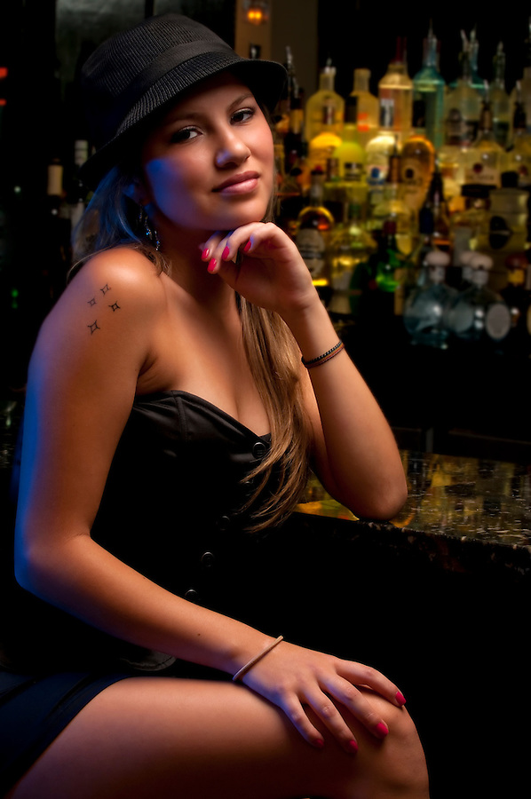 Young woman in a nightclub bar, posing very sexy.