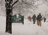 Students walk in front of Williams Hall in a snowstorm.  Winter UVM Campus