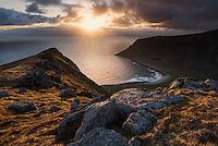 Midnight sun shines over sea from Nonstind mountain peak, Vestvågøy, Lofoten Islands, Norway