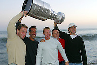 24 August 2002: Detroit Red Wings professional hockey players JIRI FISCHER, CHRIS CHELIOS, KRIS DRAPER, SEAN AVERY &amp; LUC ROBITAILLE hold the NHL Stanley Cup over their head away from the surf at sunset on the beach in the Pacific Ocean in front of Chris's summer Malibu home in Los Angeles. .