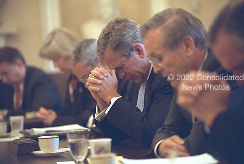 Led in prayer by United States Secretary of Defense Donald Rumsfeld, right, U.S. President George W. Bush joins his Cabinet in bowing their heads before beginning their meeting in the Cabinet Room of the White House in Washington, D.C. on Friday, September 14, 2001..Mandatory Credit: Eric Draper - White House via CNP.