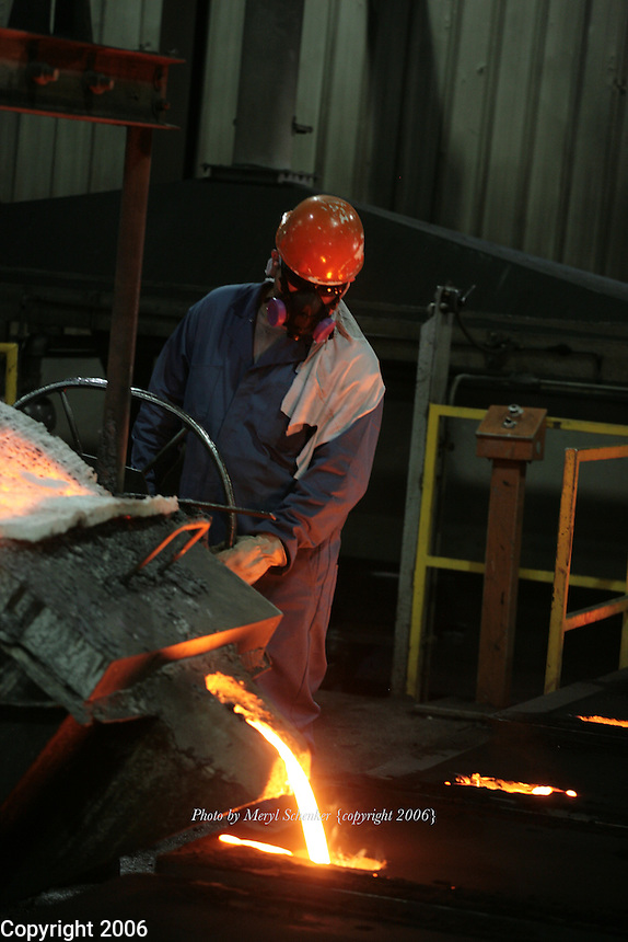 A worker at D & L Foundry in Moses Lake, Washington pours an iron mixture into manhole-cover molds on August 16, 2006. His gloves and protective suit are designed to insulate his hands, lower arms and body from temperature extremes and hot splashes fro molten metals or other hot liquids. He is also wearing a Class B hard hat and respirator.