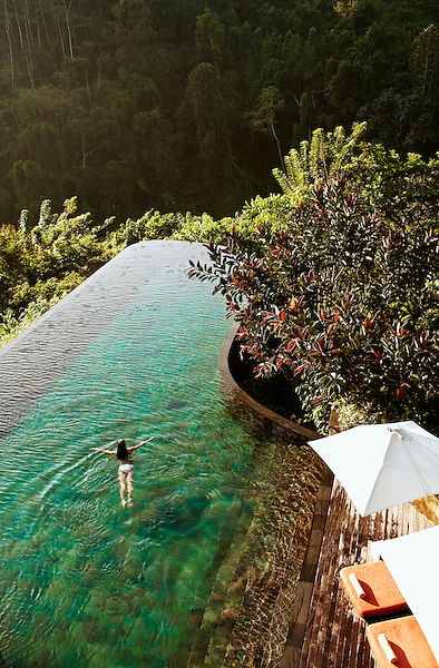 Woman swimming in infinity pool, Ubud Hanging Gardens, Bali, Indonesia. The infinity pool faces the Ayung River valley.