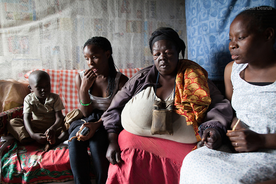 """Susan Kalai aka """"Mama Safi"""", a 53 year old Kenyan woman with severe morbid obesity, sits with her family at her home inKawangware slum in Nairobi, Kenya on December 18, 2012. """"Mama Safi""""lives on less than $1 USD a day, selling vegetables and fried potatoes in the street in front of her house. She has 7 children, the youngest one is 9 yearsold. She suffersfrom several obesity-related diseases. She can't walk, has a lot of pain in her legs and back and also has difficulties to breathe. She says """"I was born big. I was always like this.Both my parents and my sister are big too. So for me it's normal. Nothing is wrong with me"""".She has no knowledgeabout obesity and she can't go to the doctor to get treated because she has no money to pay for it. She is afraid to die of a heart attack. Although large parts of Africa areplaguedwith malnutrition, the continent must now also deal with another problem:obesity.Obesity is fast becoming a serious problem in Kenya and even the poorest are now being affected. Obesity rates are climbing around the world and they are rising faster in developing countries than in developed ones. (Photo by Benedicte Desrus)"""