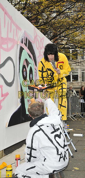 Noel Fielding.painted a billboard to promote his new book 'The Scribblings Of A Madcap Shambleton' in Golden Square, London, England, UK, 26th November 2011..photocall full length  pink paint brush painting mural  yellow boiler suit  heart graffiti step ladder  silver heels boots heels microphone .CAP/CAN.©Can Nguyen/Capital Pictures.