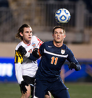 Alex Shinsky (9) of Maryland applies pressure to Eric Bird (11) of Virginia during the NCAA Men's College Cup semifinals at PPL Park in Chester, PA.  Maryland defeated Virginia, 2-1.