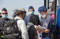 Police officers register migrants getting on buses after crossing the border between Serbia and Hungary before the last opening is closed near Roszke (about 174 km South of capital city Budapest), Hungary on September 14, 2015. ATTILA VOLGYI