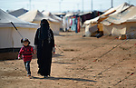 A woman and her daughter walking in the Zaatari Refugee Camp, located near Mafraq, Jordan. Opened in July, 2012, the camp holds upwards of 50,000 refugees from the civil war inside Syria. International Orthodox Christian Charities and other members of the ACT Alliance are active in the camp providing essential items and services.