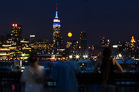 People look at the full moon while it rises next to the Empire State Building in New York City seen from Hoboken in New Jersey,  Aug 21, 2013. Photo by Eduardo Munoz Alvarez / VIEWpress.
