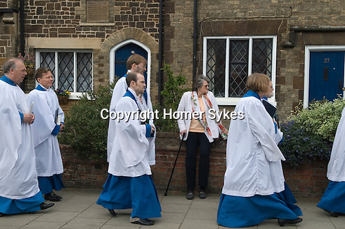 Wilkes Walk is an annual procession to the Almshouses on North Street in Leighton Buzzard Bedfordshire Uk. <br /> <br /> It takes place every Rogation Sunday  in memory of Edward Wilkes who founded the Almshouses in the seventeenth century and died in 1646.  His son, Matthew, left funds to be devoted to this annual commemoration.<br /> The procession includes a garland bearer, clergy, Almshouse officials and the choir of All Saints Church; after a short service a reading is taken from Wilkes&rsquo; Will, while one of the choir members stands on their head  as is stipulated in the Will.  At the Alms Houses the choir sings a short anthem, prayers are read in thanksgiving for the Wilkes family and part of the will is read aloud. While this is done a member of the choir must stand upon his or her head. Each member of the Alms Houses also receives a small remuneration to celebrate the day.<br /> Afterwards, refreshments, beer and a light lunch provided at the Market Cross. This became very unrully and was abandoned many years ago. Buns, soft drinks and tea are provided back aat the church instead. The young members of the choir are given a &pound;1 and the Vicar gets &pound;50, which he gives to Save the Children Charity.<br /> Many rogationtide boundary marking customs involve youngsters being bumped, upended or  whipped at set boundary points to help them remember the location of the landmarks, and perhaps the head-stand derives from this