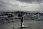 A small child standing alone on the beach with a rough sea