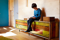 The artist Richard Woods has built a timber house where he can both create and showcase his bold, bright work.  Woods shares with his wife Jess Spanyol, a children's book author, and their three children. 10-year-old  Lorcan sits and reads on a cabinet faced with his father's Woodgrain pattern.