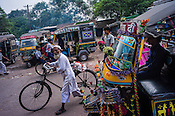 A cyclist walks past an auto at the busy marketplace in Jharia, outside of Dhanbad in Jharkhand, India.  Photo: Sanjit Das/Panos