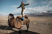 Malang Daryo (Wakhi guide and first climber on Noshaq, Afghanistan's highest mountain) playing with a  Bactrian camel..Ech Keli, Er Ali Boi's camp, one of the richest Kyrgyz in the Little Pamir..Trekking with yak caravan through the Little Pamir where the Afghan Kyrgyz community live all year, on the borders of China, Tajikistan and Pakistan.